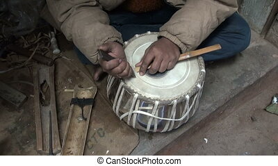 drum master working with new tabla - drum craftsman working...