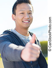 Happy Asian Man Showing Thumb Up Sign - Happy Young Asian...