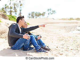 Young Couple Sitting On Beach And Looking At View