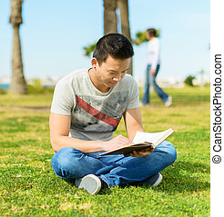 Man Reading Book In Park - Young Man Reading Book In Park;...