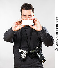 Casual Caucasian photographer, about 40 years old with two cameras and a smart phone taking pictures. Studio portrait.