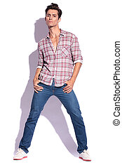 man poses with legs spread - portrait of a young casual man...