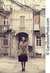 Redhead girl on the yard with suitcase in Odessa.