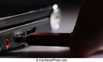 Inserting red usb flash drive in notebook Macro shot -...