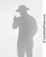 man with cowboy hat smoking a cigarette, silhouette