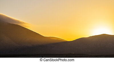sunrise over Femes mountains seen from Playa Blanca,...