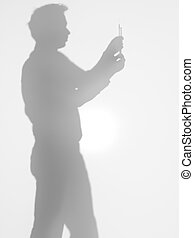 medical assistant holding a syringe, silhouette - side view...