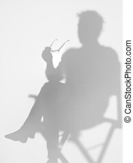 man sitting on director's chair, silhouette - man sitting on...