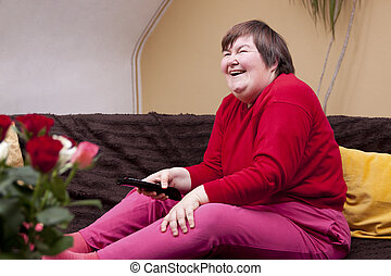 Mentally disabled woman watching television and enjoys -...