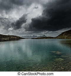 Stormy lake - Mountain lake with storm and dark clouds,...