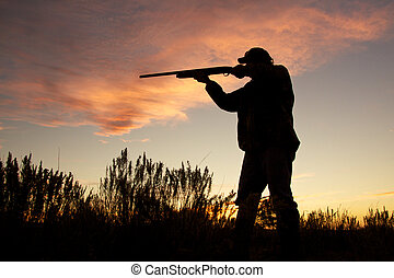 Shooting in the Sunrise - a bird hunter shooting his shotgun...