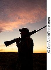 Shotgun Ready at Sunrise - a bird hunter with shotgun in the...