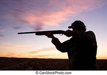 Shooting at Sunrise - a bird hunter shooting shotgun...