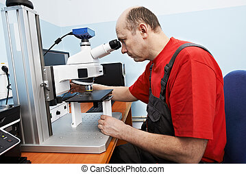 worker checking probe with industrial microscope -...
