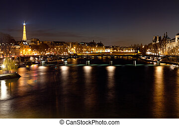 Pont des Arts in Paris at night - pamorama of Seine River...