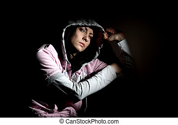 Girl in hood - Young white girl sitting looking sad wearing...