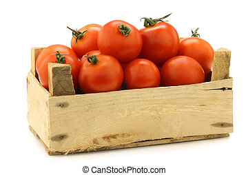 fresh tomatoes on the vine in a wooden crate on a white...
