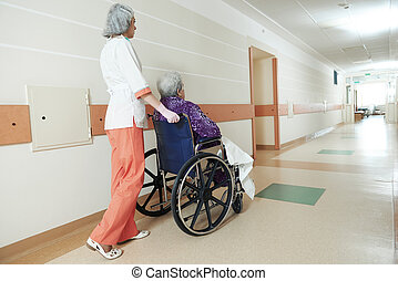 Nurse with elderly patient in wheelchair - female nurse...