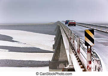 Two Cars at a Bridge under Muddy River in Iceland. Overcast...