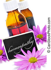 homeopathy - some dropper bottles and a blackboard with the...