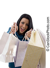 front view of cheerful woman showing carry bags against...