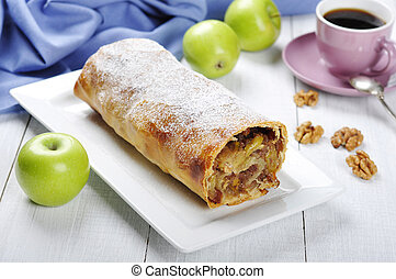 apple strudel on a dish with fresh apples and cup of coffee