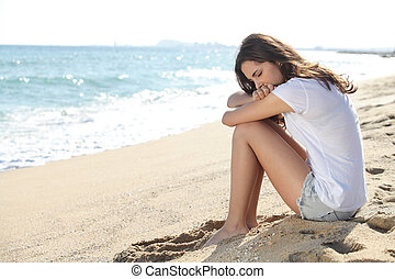 Portrait of a worried girl sitting on the beach with the sea...