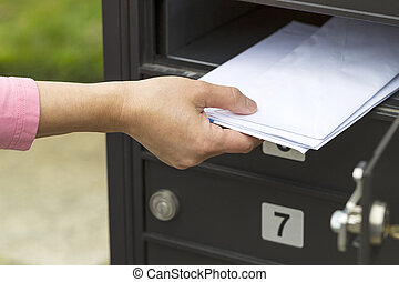 Putting up the mail - Horizontal photo of female hand...