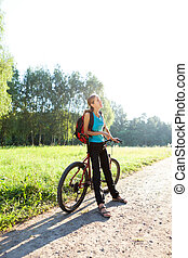 Woman cyclist on walking with bicycle in spring nature