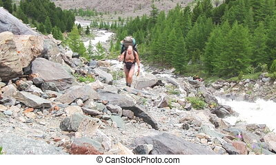 Man with backpack hiking across mountain
