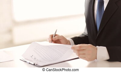 man signing a contract while female assistaint brings a cup...