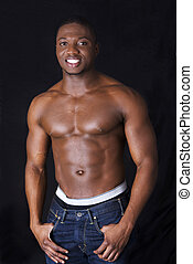 Muscular black man, against black background