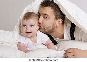 Father and child - Young father is playing with baby in bed