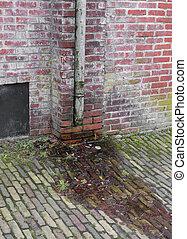 rain gutter - old rain gutter along a brick wall
