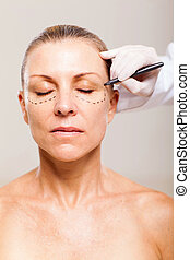 beautician draw correction line middle aged woman face -...