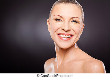 mid age woman smiling against black background