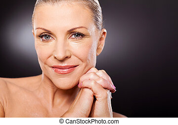 mid age woman close up portrait over black background -...