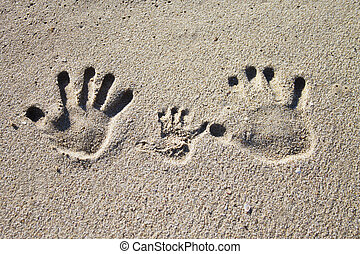 Family palm imprints on sand - Three palm imprints of family...