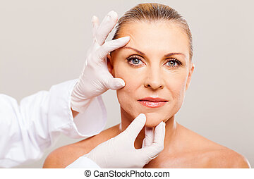 skin check before plastic surgery - surgeon doing skin check...