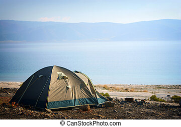 Camping tent in the nature by lake