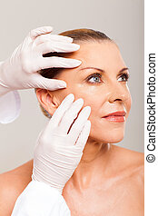 skin check on mid age woman face - doctor doing skin check...