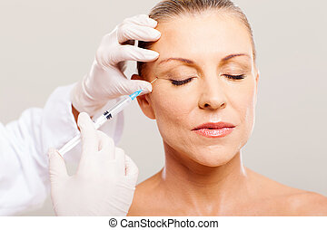 beautician giving face lifting injection on mature woman