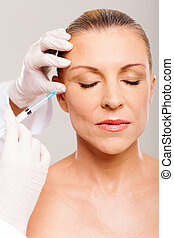 cosmetic surgeon injecting mid age woman face