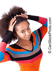 Black African American teenage girl holding her afro hair,...