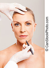 cosmetic surgeon marking mid age woman chin before plastic...