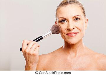 beautiful mature woman applying make up - portrait of...
