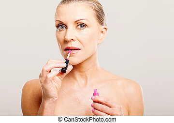 older woman putting lip gloss - portrait of older woman...