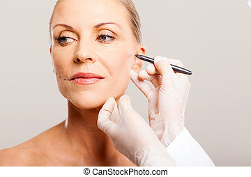 doctor correcting senior woman face - doctor drawing...