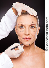 doctor marking senior woman face for plastic surgery