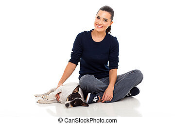 young woman sitting on floor with her dog - smiling young...